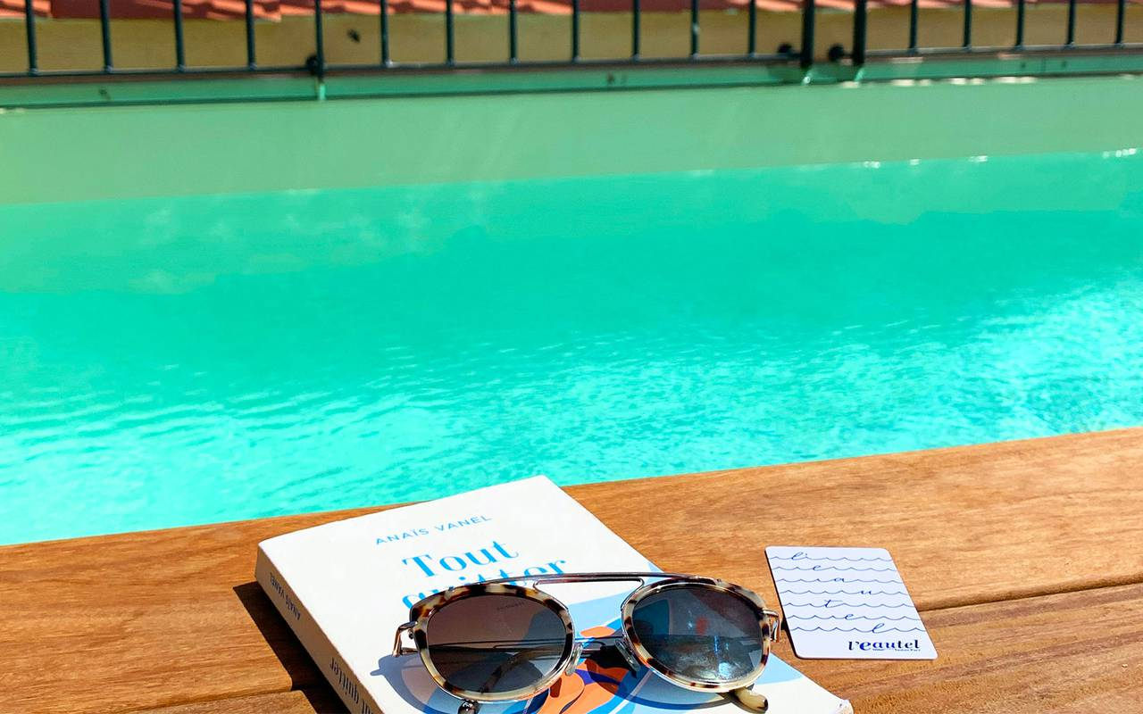 book and sunglasses in front of the pool in our hotel spa in Toulon