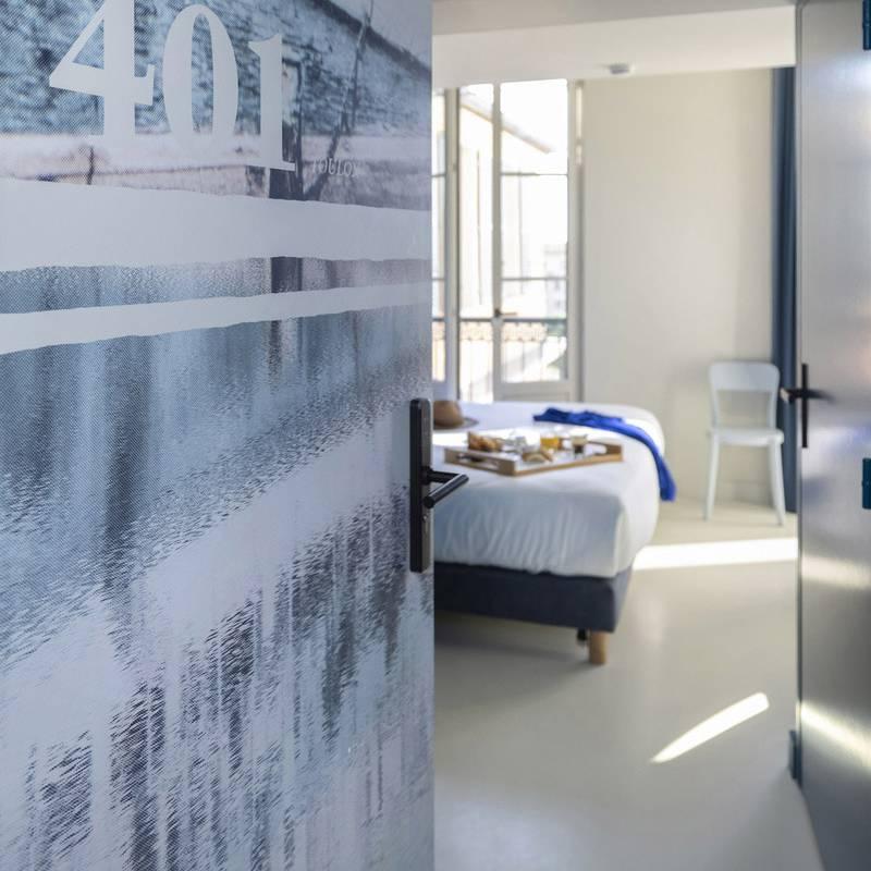 Porte ouverte sur la chambre, hôtel Toulon centre, l'Eautel